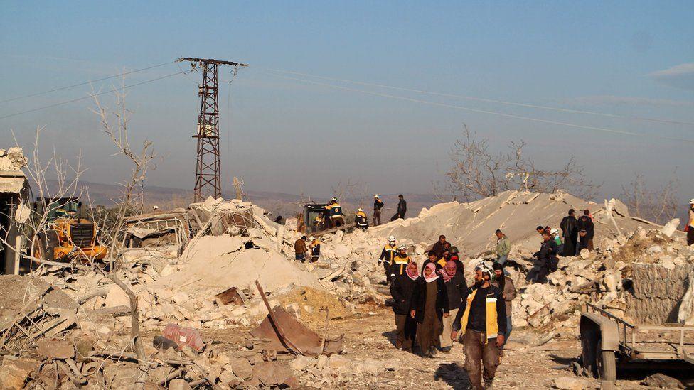 Rescuers and civilians walk through rubble