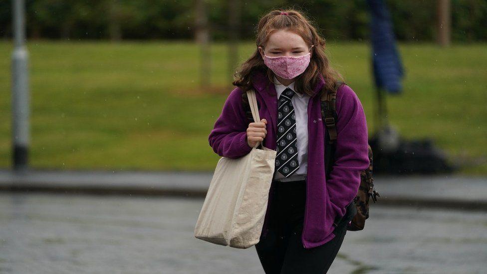 A schoolgirl wearing a mask