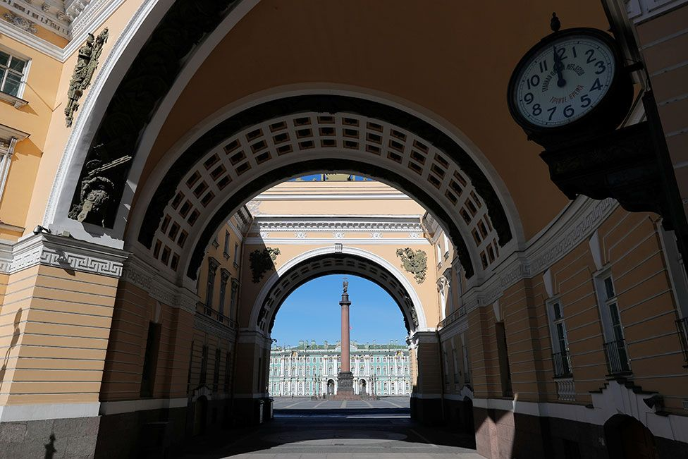 A clock showing the time at noon by The State Hermitage museum in front of Palace square in Saint Petersburg, Russia