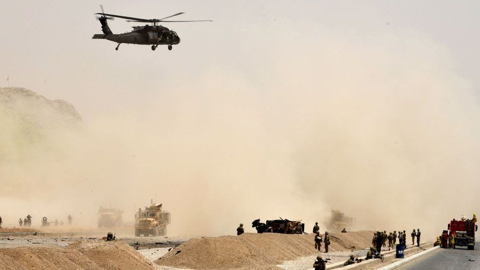 A US black hawk helicopter flies over the site of a Taliban suicide attack in Kandahar