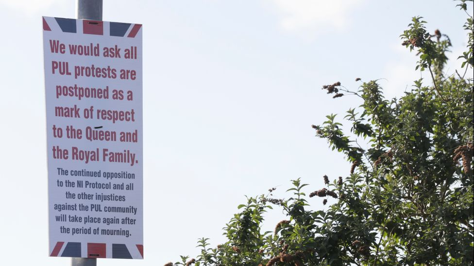 A sign showing a message to loyalist protesters to delay their protests as a sign of respect