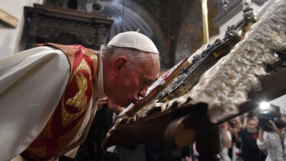 Pope Francis kisses the Holy Book as he visits the Apostolic Cathedral in Etchmiadzin, outside Yerevan, on 24 June