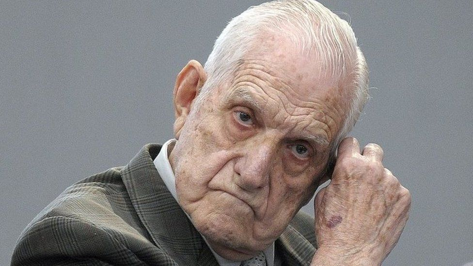 In this file picture taken on April 20, 2010, former Argentine de facto president and Army chief Reynaldo Bignone gestures at the courtroom before being sentenced during his trial, in Munro, Buenos Aires