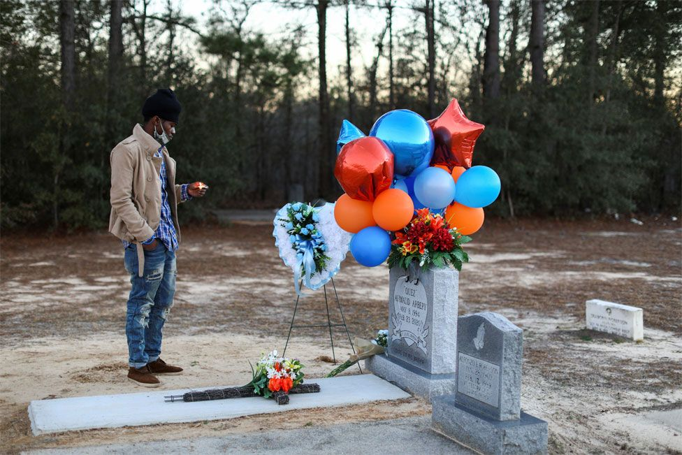 A man holds a candle next to a grave that is covered in flowers and balloons