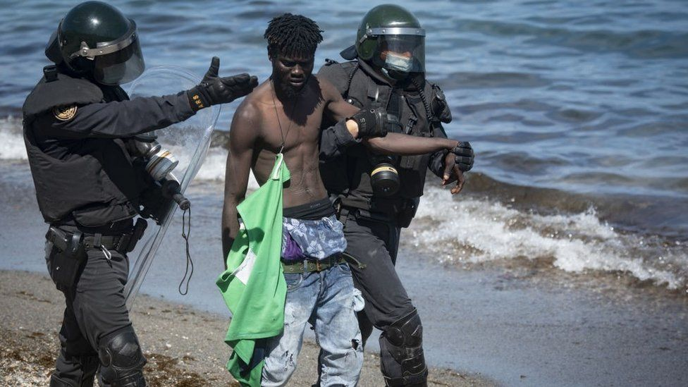 Spanish soldiers stand guard and intervene as migrants arrived swimming to Spanish territory of Ceuta on May 18, 2021