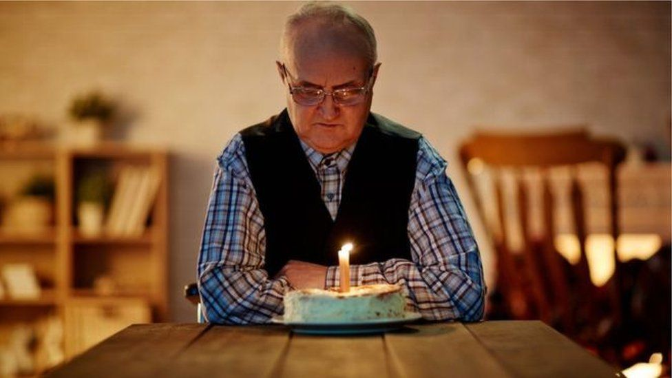 A man on his own with a birthday cake