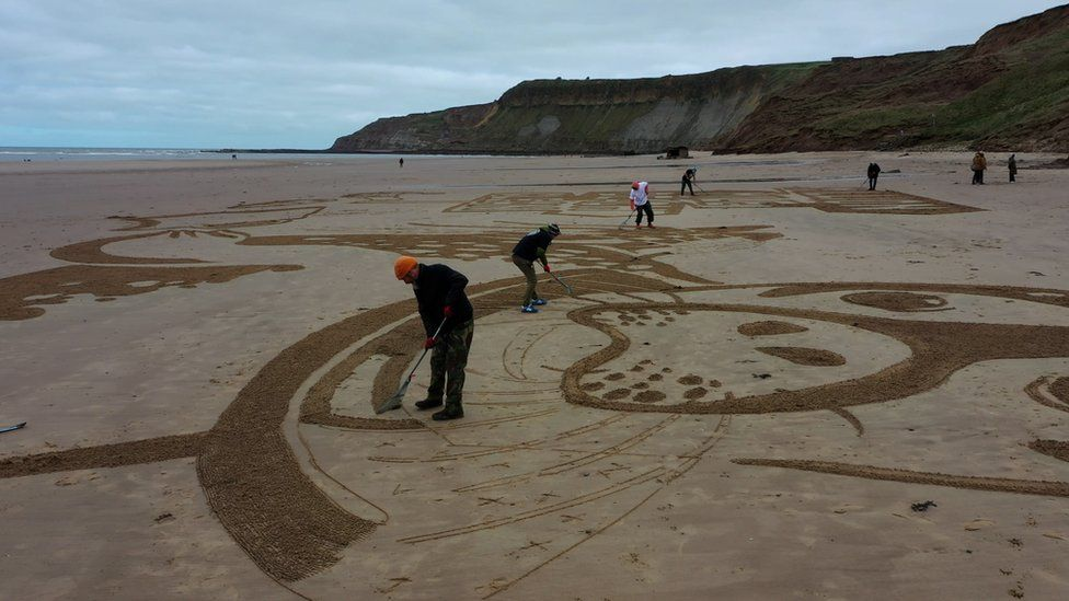 People creating a sand drawing