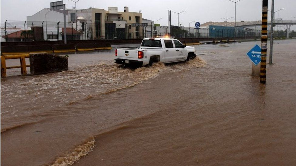 A truck drives along a flooded street in Manzanillo, Colima state, Mexico on October 23, 2015, during hurricane Patricia.