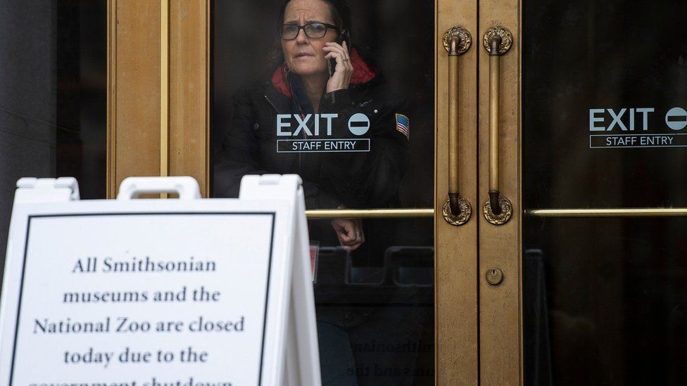 A US government employee talks on the phone as she looks out of a closed Smithsonian museum in Washington, DC on January 18, 2019