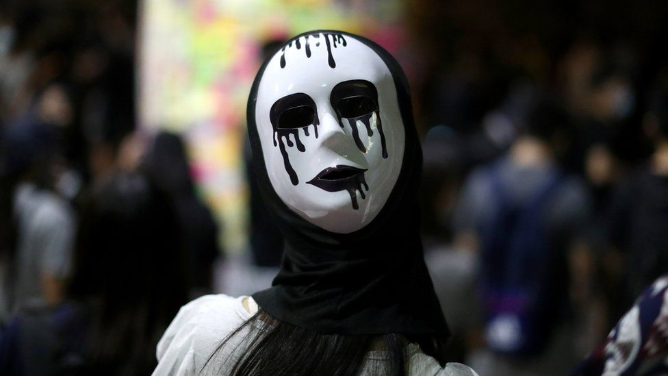 An anti-government protester wears a mask during a demonstration in Wong Tai Sin district, in Hong Kong