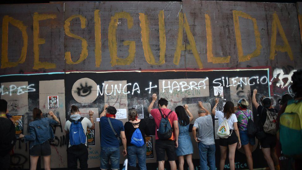 """People demonstrate under graffiti reading """"Inequality"""" during a protest demanding greater social reforms from Chilean President Sebastian Pinera in Santiago on 12 November, 2019."""