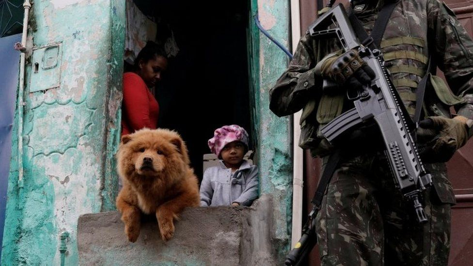Armed Forces members patrol, as residents watch, during an operation against organized crime in Manguinhos slum complex in Rio de Janeiro, Brazil, August 21, 2017.