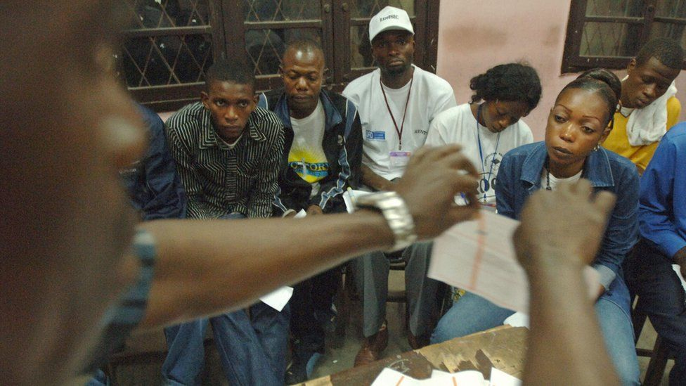 An official raises a used ballot paper while counting votes during an election in the Democratic Republic of Congo, 29 October 2006