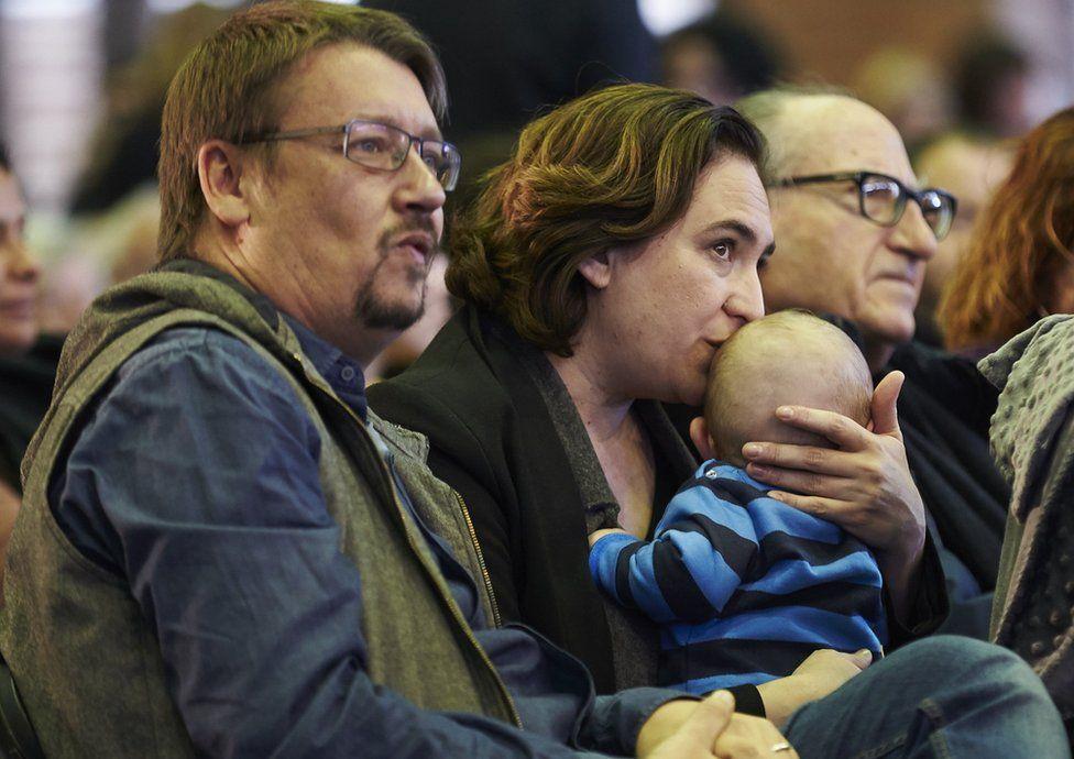 Ada Colau kisses her baby next to Xavier Domenech in Barcelona, 11 November