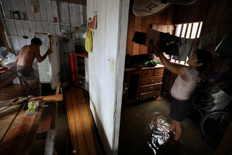 Manoel de Oliveira Cardoso and his wife Eliana dos Santos Madi clean up their flooded house by the rising Solimoes river