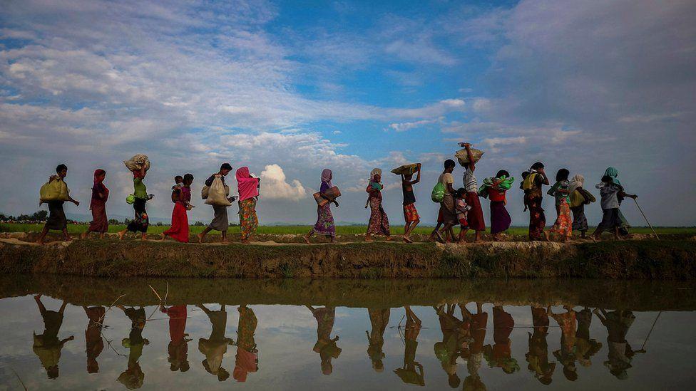 Rohingya refugees walking along a lakeside in Bangladesh