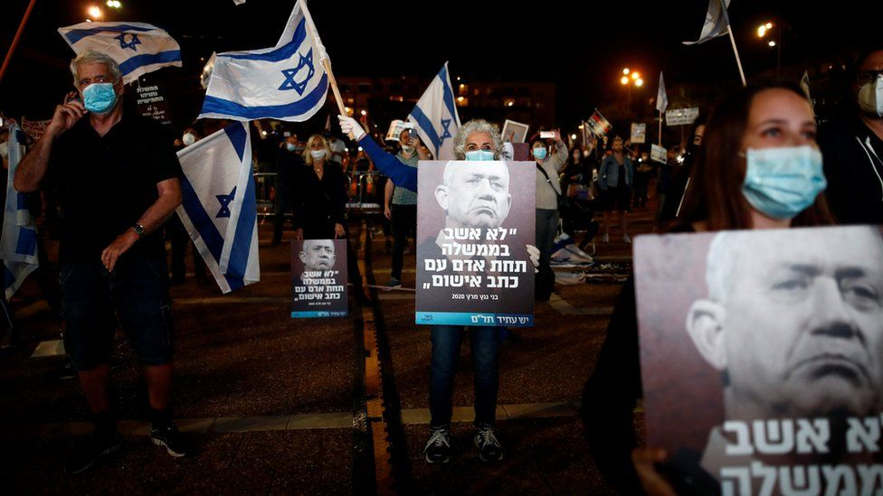 "People hold up posters showing Benny Gantz and quoting him as saying: ""I would not sit in a government under a man facing criminal indictment"" at a protest in Tel Aviv on 19 April 2020"