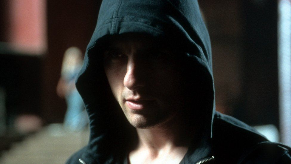 Tom Cruise glowers from beneath a black hoodie in this still from the film Minority Report