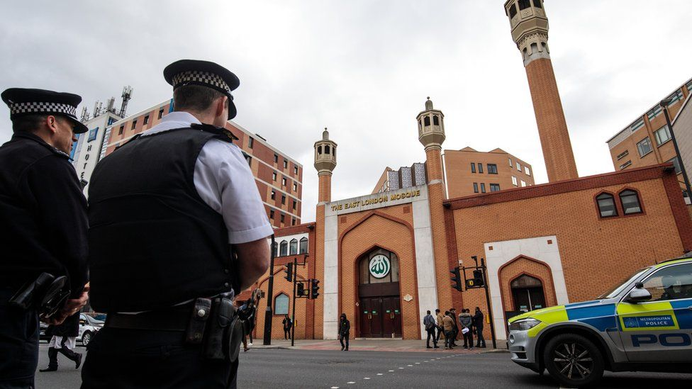 Police officers stand on patrol outside the East London Mosque