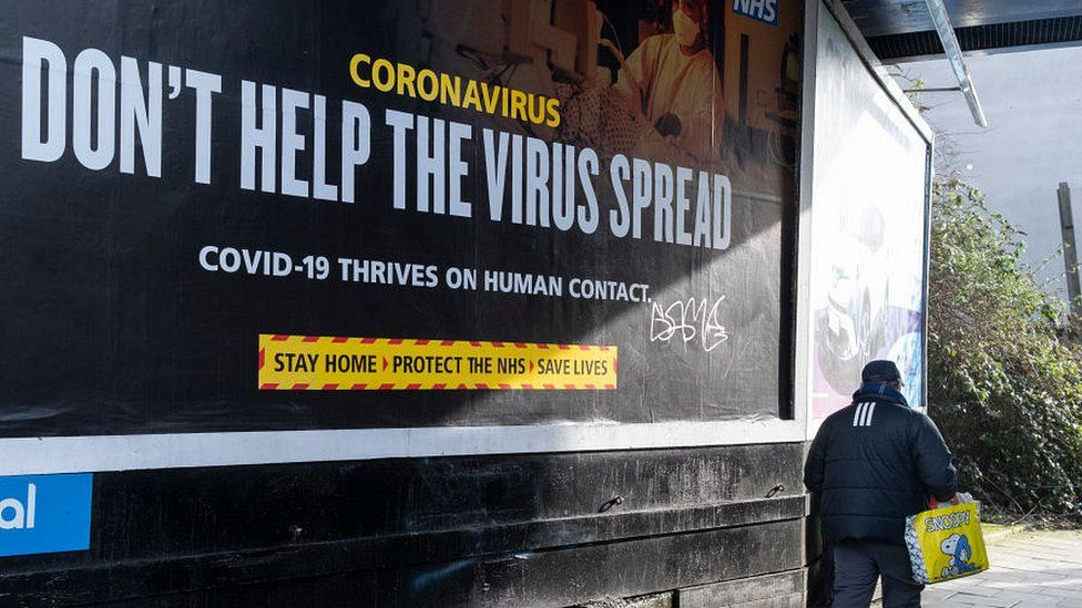 man walking past Covid billboard don't help the virus spread