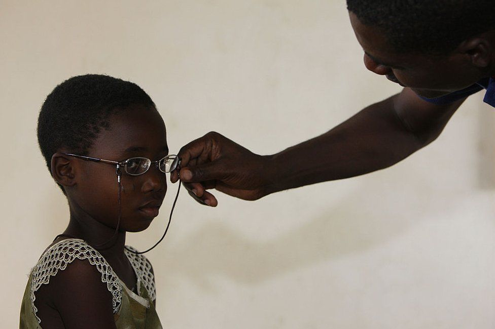 A child tries on a new pair of glasses in Togo