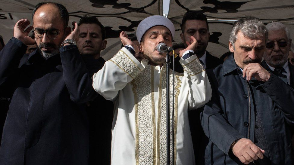 An imam recites verses from the Koran under a tent set up to protect against the rain in Istanbul