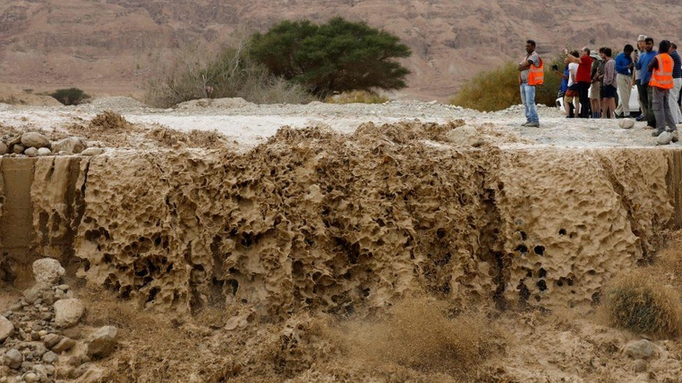 Israelis watch flooded water running through a valley, blocking the main road along the Dead Sea in the Judean desert