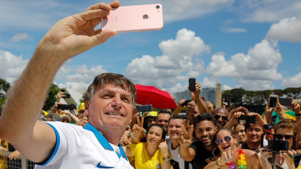 Brazilian President Jair Bolsonaro takes a selfie with supporters in front of the Planalto Palace