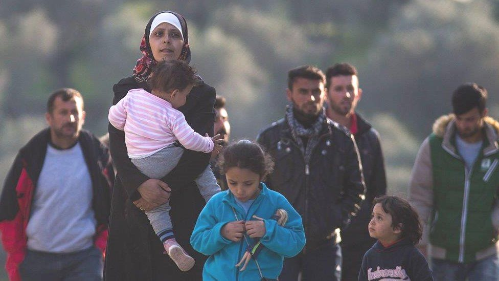 Refugee and migrant families walk through the Moria Refugee Camp in 2016