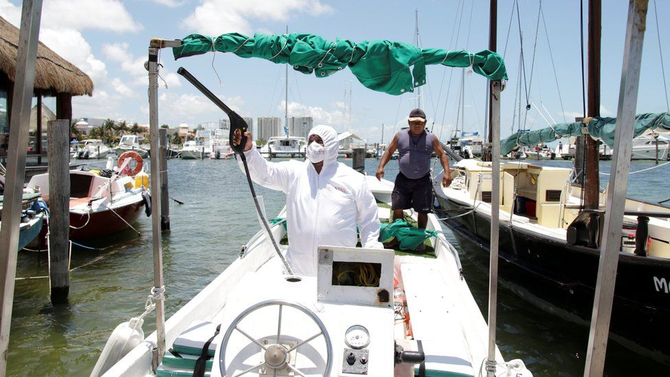 An employee of a private company disinfects a boat at a marina in Cancun