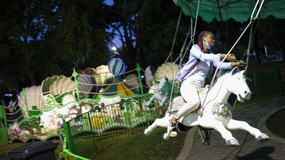 A woman sits on a white horse at a fairground.