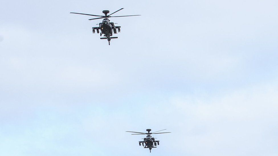 Two Apache helicopters flying in the air