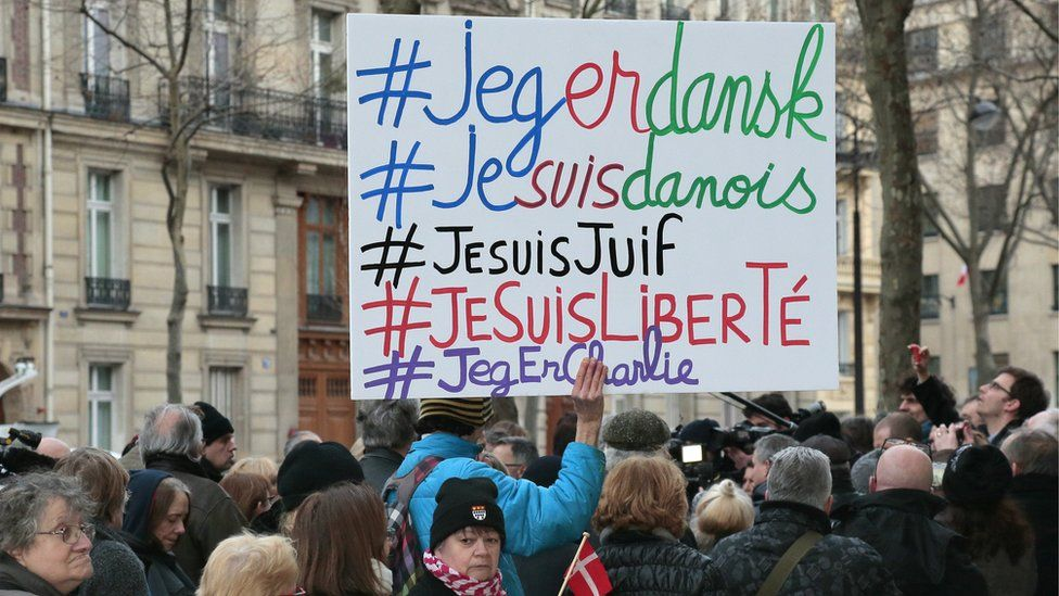 A man holds a placard with the hashtags 'I am Danish, I am Jewish, I am Freedom' next to a woman holding a Danish flag outside the Danish Embassy in Paris