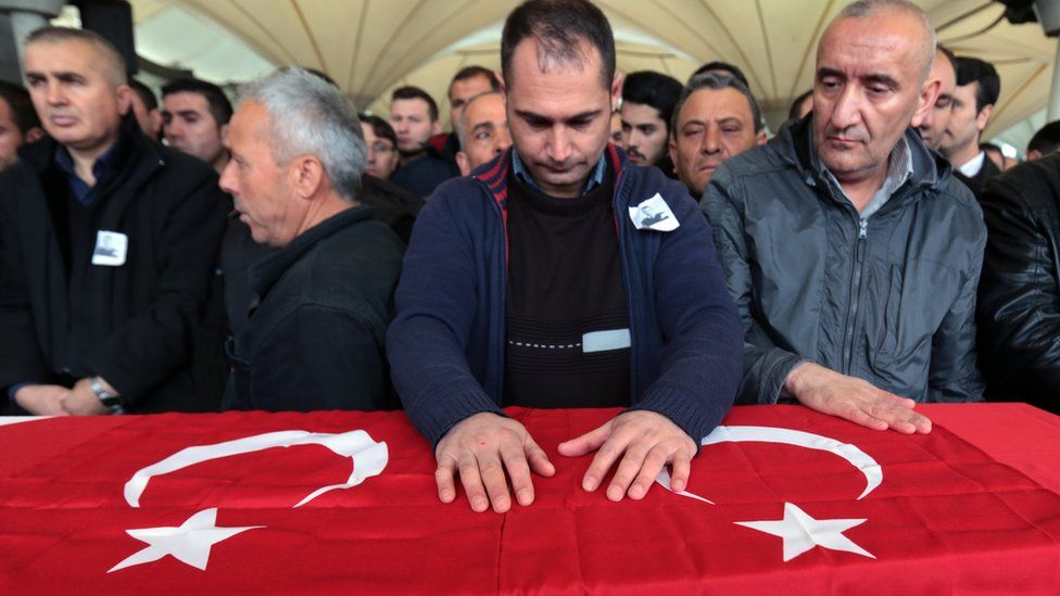 People stand by a coffin draped in a Turkish flag for a Turkish security agent killed in a suicide blast