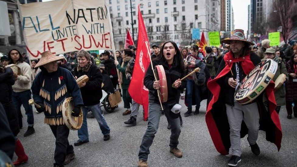 Alex Spence beats a drum and sings during a march in support of pipeline protesters in Vancouver