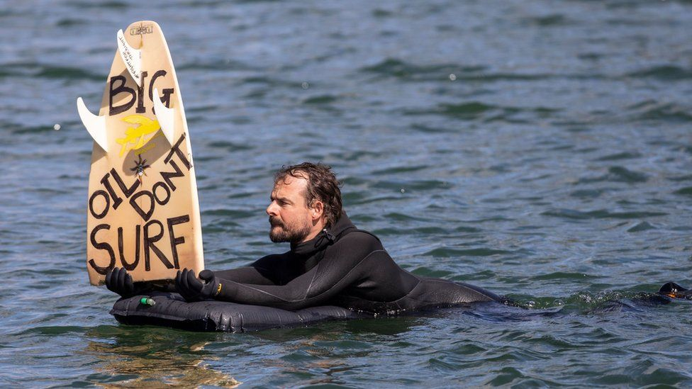 "A protester in the harbour in Oslo, Norway holds up a surfboard with the political message: ""Big Oil Don't Surf"""