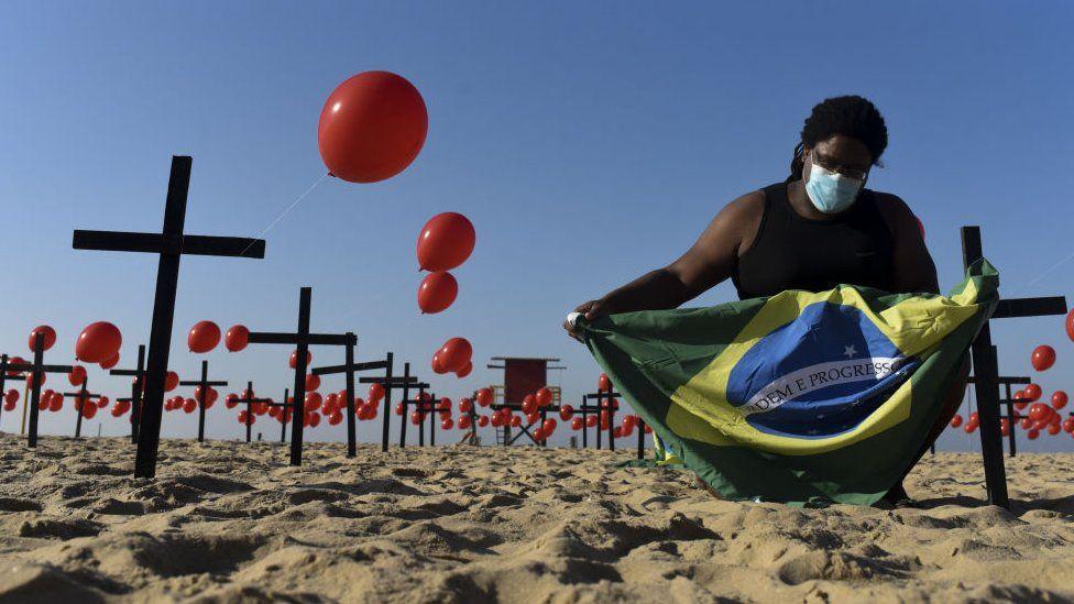 Homem segura bandeira do Brasil em meio a balões vermelhos, representando vítimas de covid-19, no Rio de Janeiro