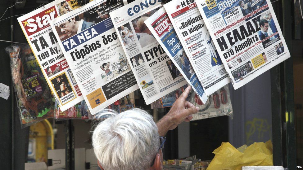 A man inspects the morning papers in Athens