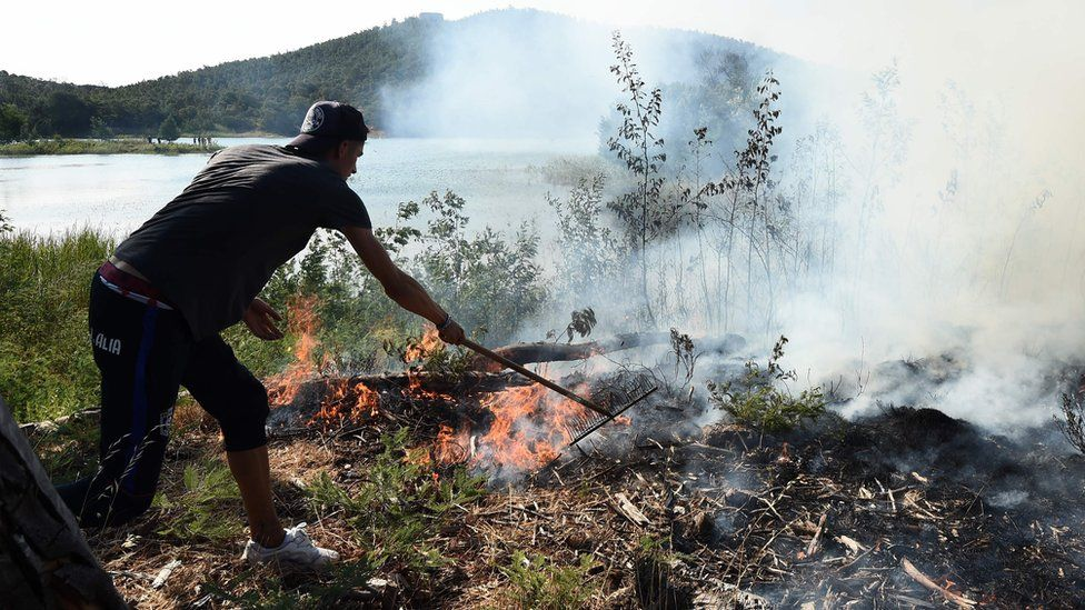 A man tries to extinguish a fire burning in Bormes-les-Mimosas, south-eastern France, on July 26, 2017