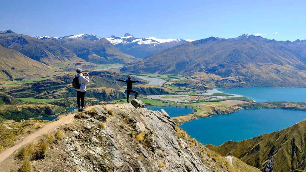 Tourists taking pictures of the views of Lake Wanaka from Roy's peak.