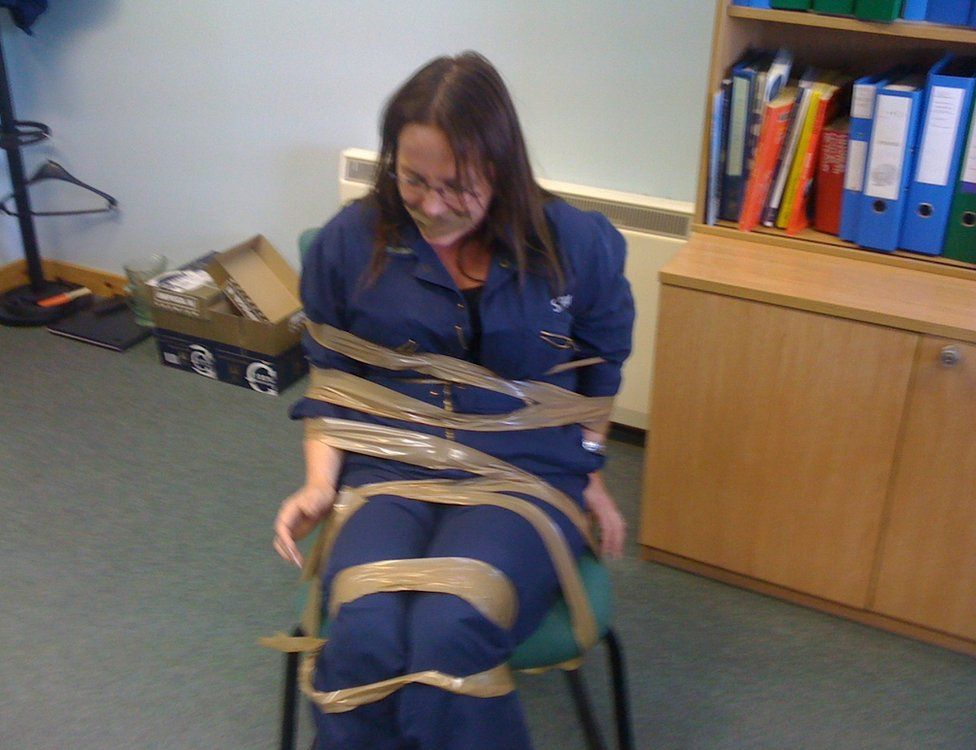 DeeAnn Fitzpatrick taped to a chair