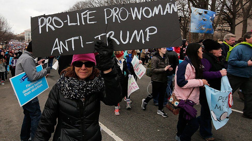 Woman with a 'pro-life, pro-woman, anti-Trump' placard