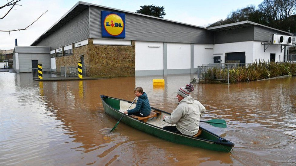Two people in canoe rowing by a Lidl store in Monmouth