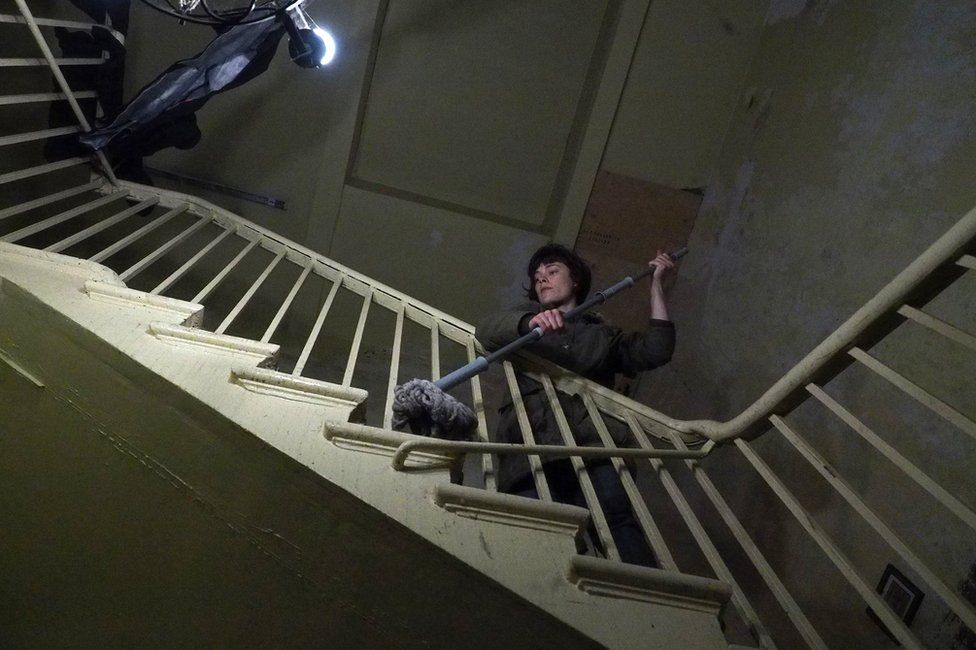 A woman cleaning a staircase with a mop