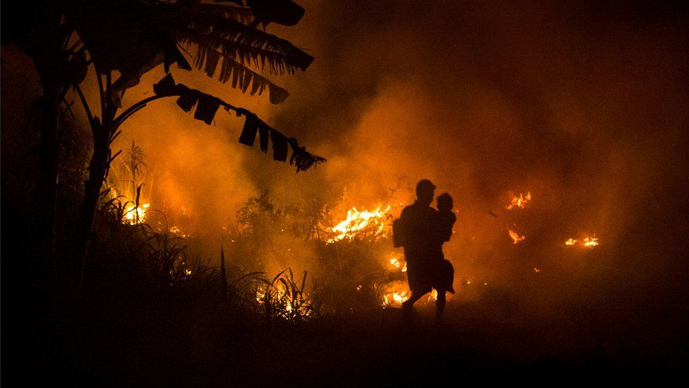 A man and child walk past burning forests