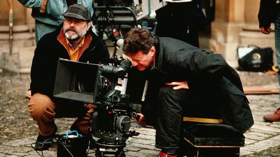 John Madden peers into the viewfinder of a large-format film camera on the ground, surrounded by other crew