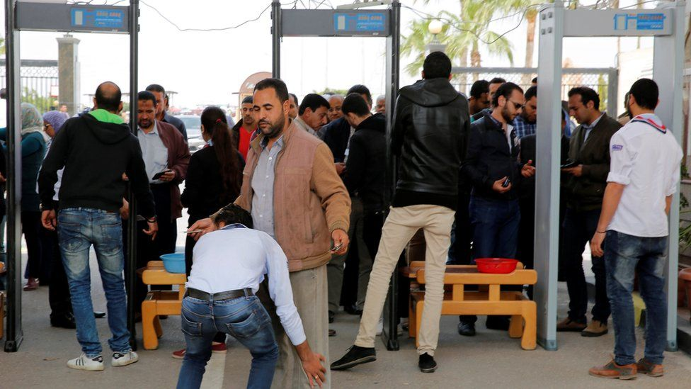 Mourners go through security checks outside the Monastery of St Mina in Alexandria