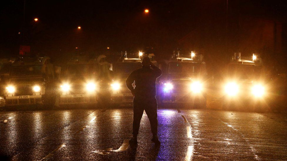 A man stands facing a line of police armoured Land Rovers