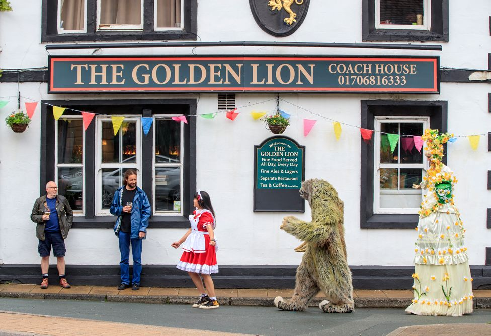 People in costume entertain pub customers on the street
