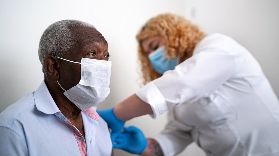 older black man being given vaccine